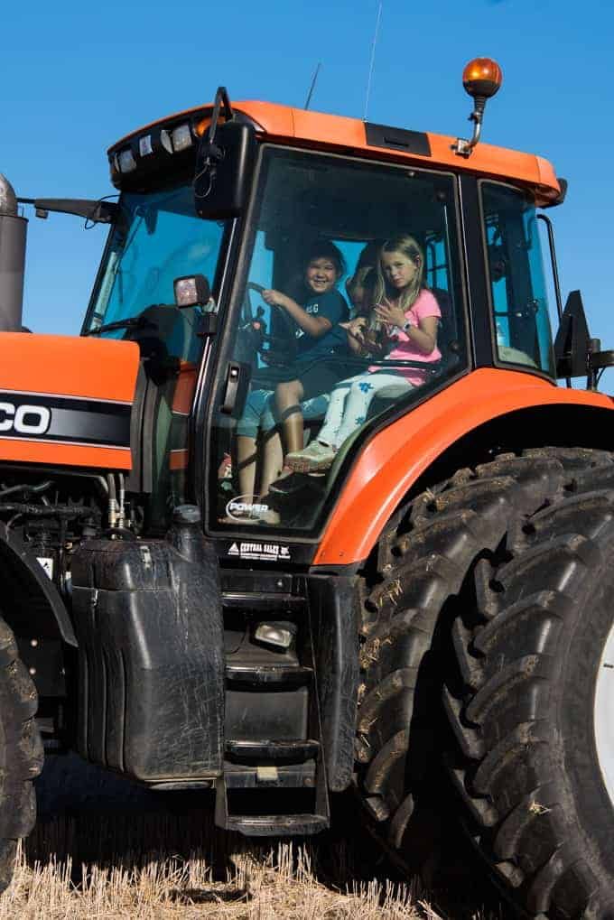 Kids learning to drive a tractor.