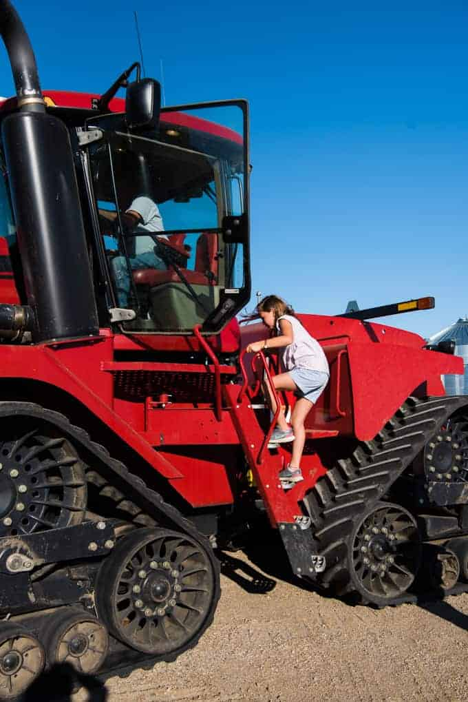 A girl climbing into the cab of a large red tractor.