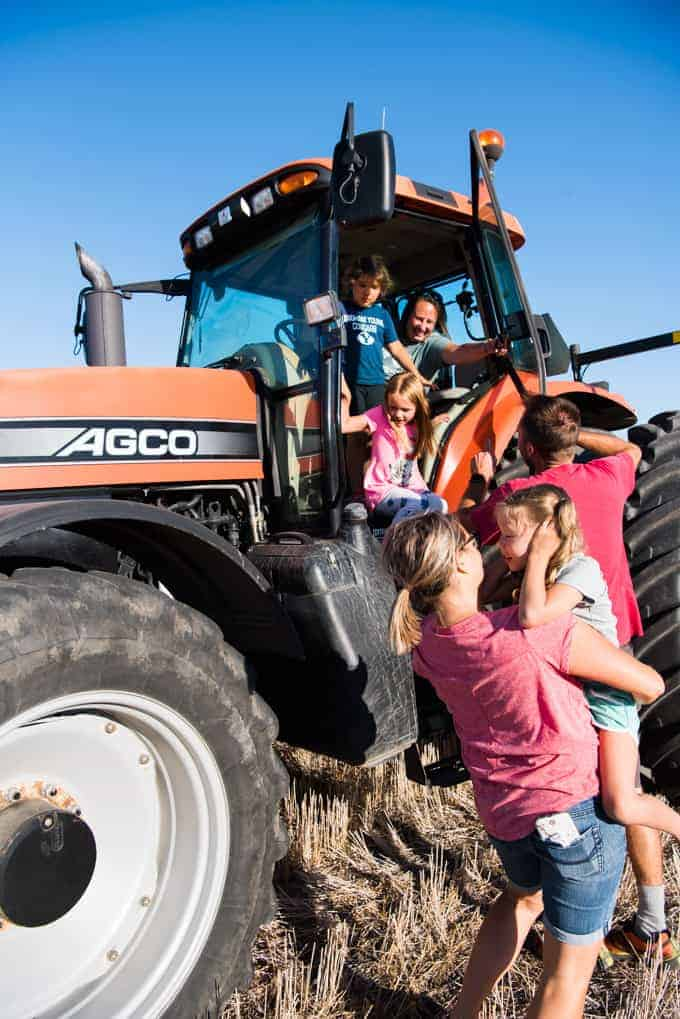 Kids climbing out of the cab of a big tractor.