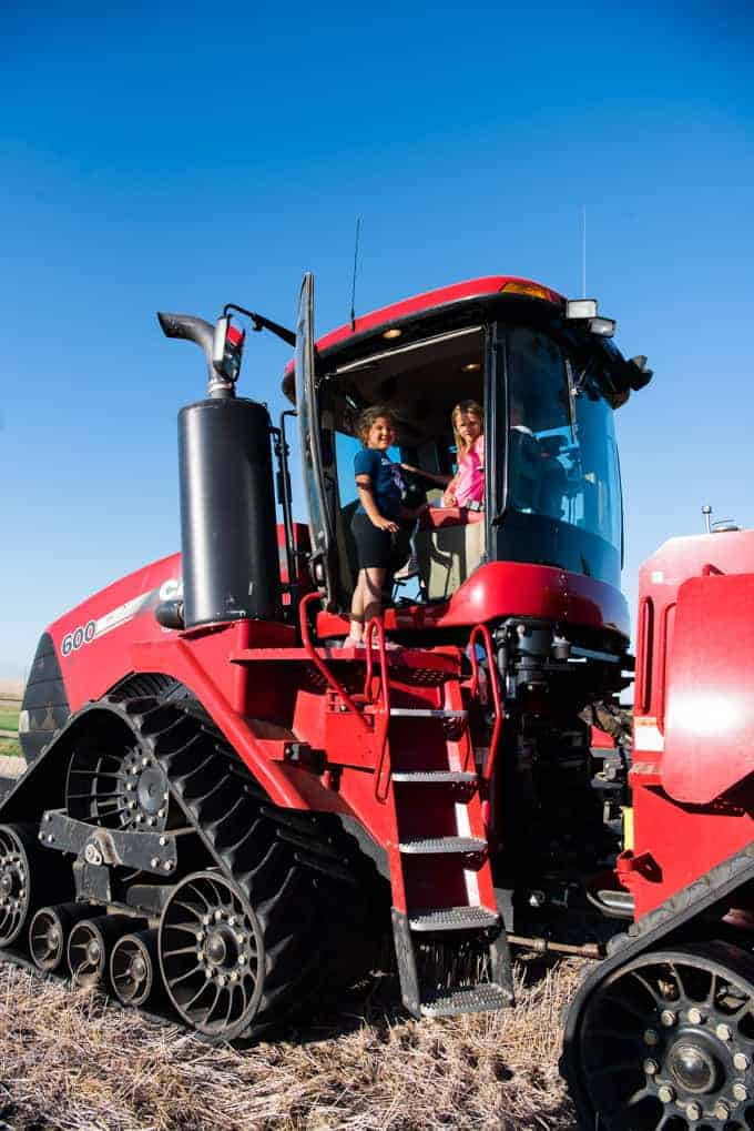 Children sitting in a large red tractor.