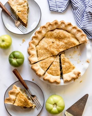 Slices of green tomato pie on dessert plates with forks next to the rest of the pie in a white pie plate.