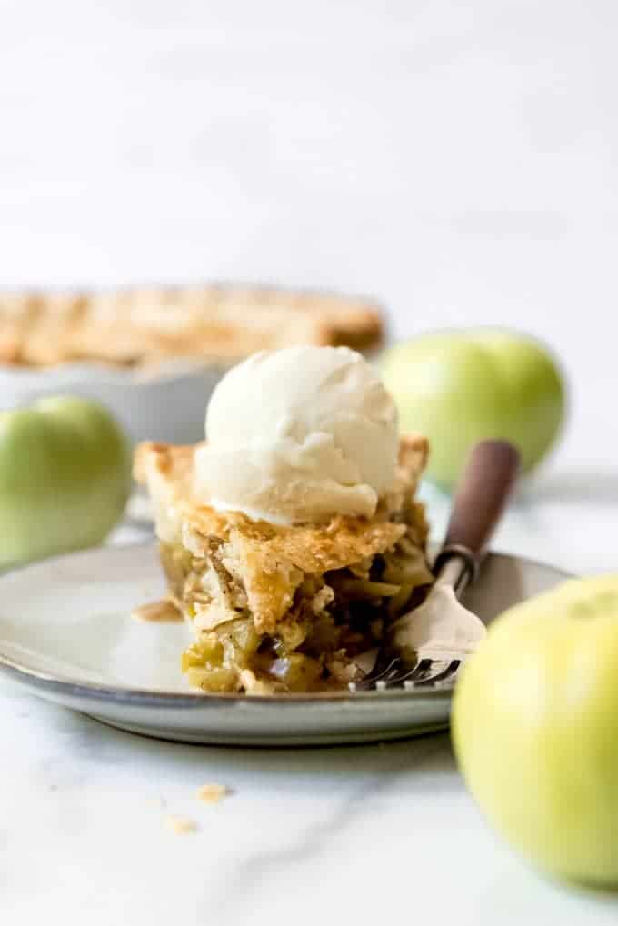 A slice of green tomato pie on a plate with a scoop of vanilla ice cream and a fork.
