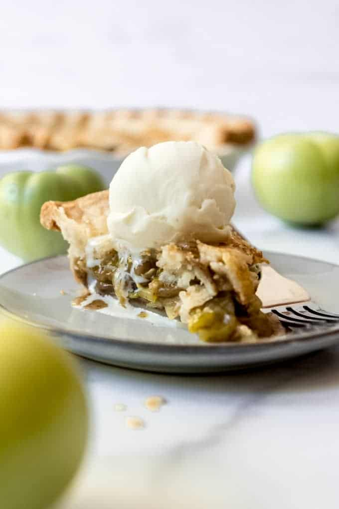 A slice of green tomato pie on a plate with a scoop of vanilla ice cream melting on top.
