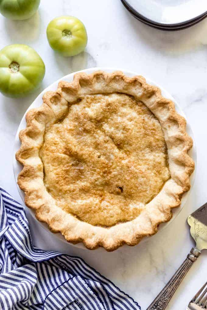 An overhead image of a pie with coarse sugar on top next to green tomatoes.