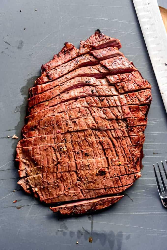 Flank steak sliced against the grain on a cutting board.