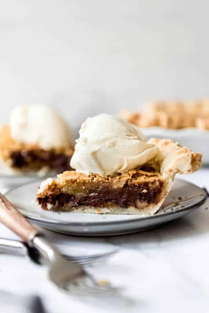 A side-angle image of a slice of Kentucky Chocolate Walnut Pie on a plate with a scoop of vanilla ice cream on top.