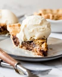 A slice of Kentucky Derby Day Pie with a scoop of vanilla ice cream melting on top.