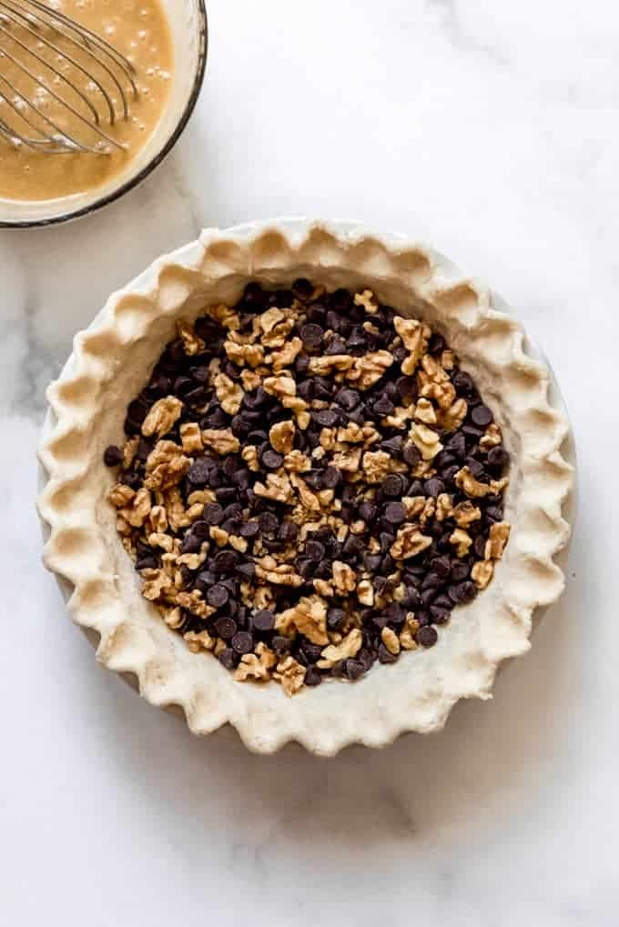 An unbaked pie crust filled with chopped walnuts and chocolate chips.