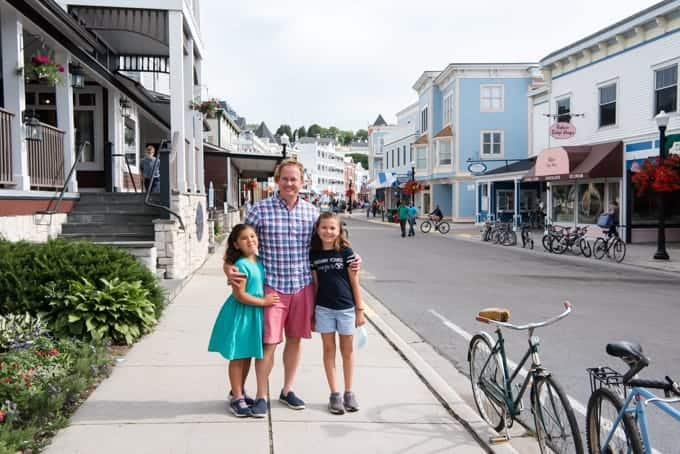A father and two daughters on the main street on Mackinac Island.