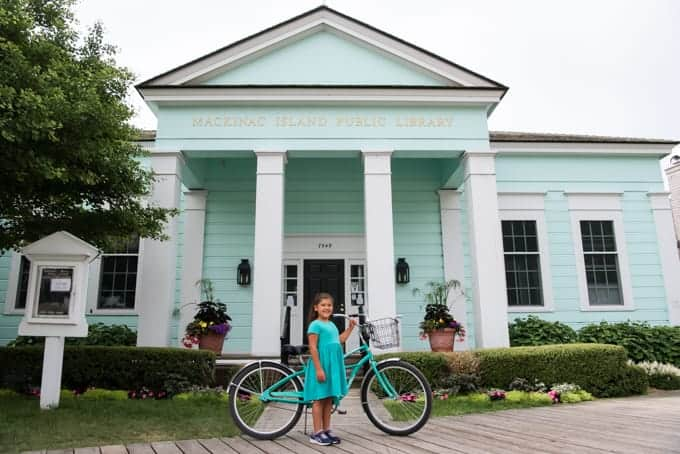 A child with a bicycle in front of the Mackinac Island Public LIbrary.
