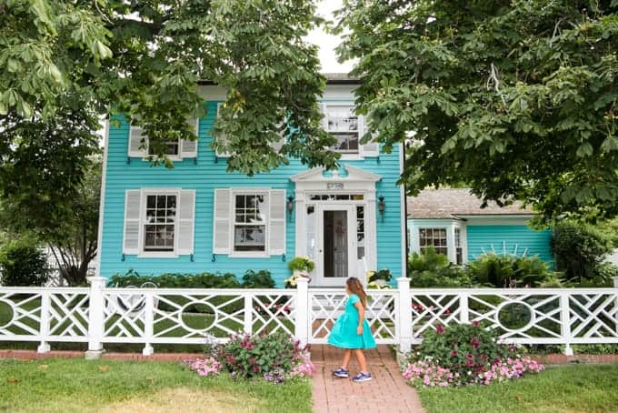 A child in a turquoise dress in front of a turquoise house.