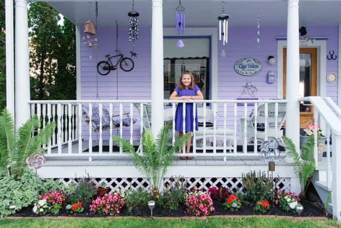 A child in a purple dress in front of a purple house.