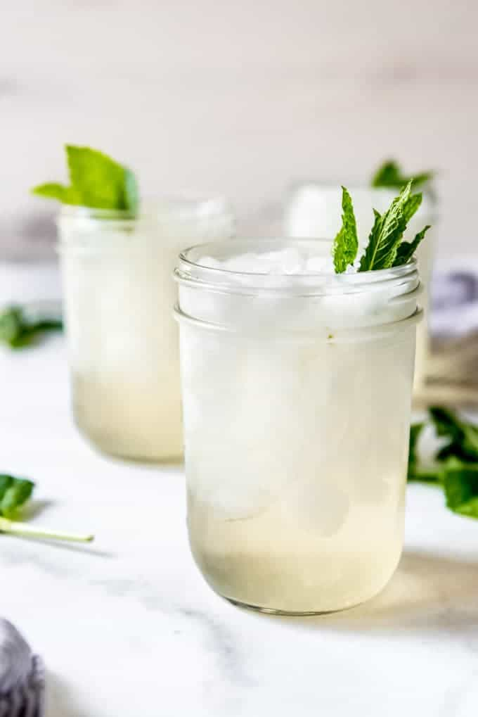 Glass mason jars filled with crushed ice for mint juleps garnished with mint leaves.