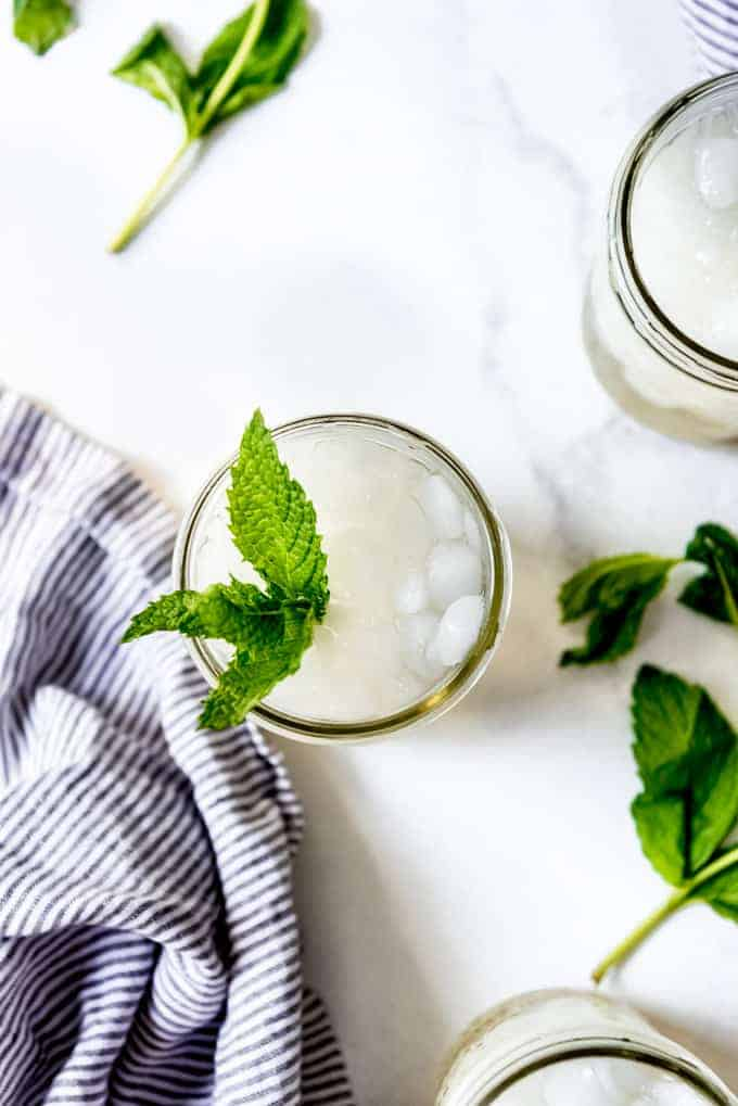An overhead image looking into a glass of non-alcoholic mint julep with mint leaves next to a striped napkin.