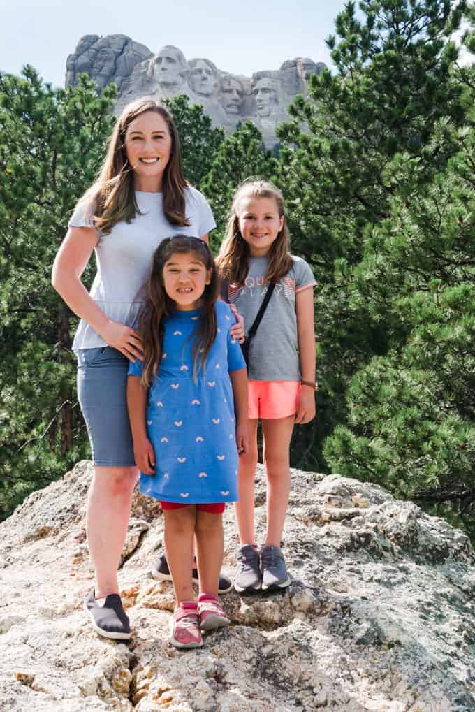 A mother and daughters in front of Mt. Rushmore.
