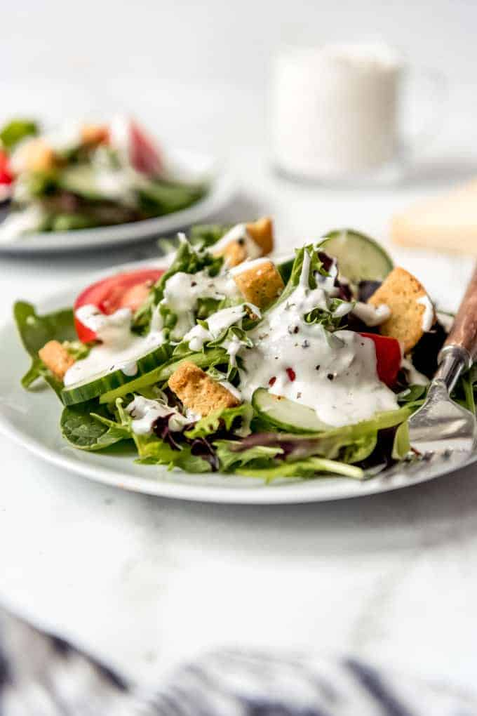 A green salad with cucumbers, tomatoes, croutons, and parmesan peppercorn dressing on top.