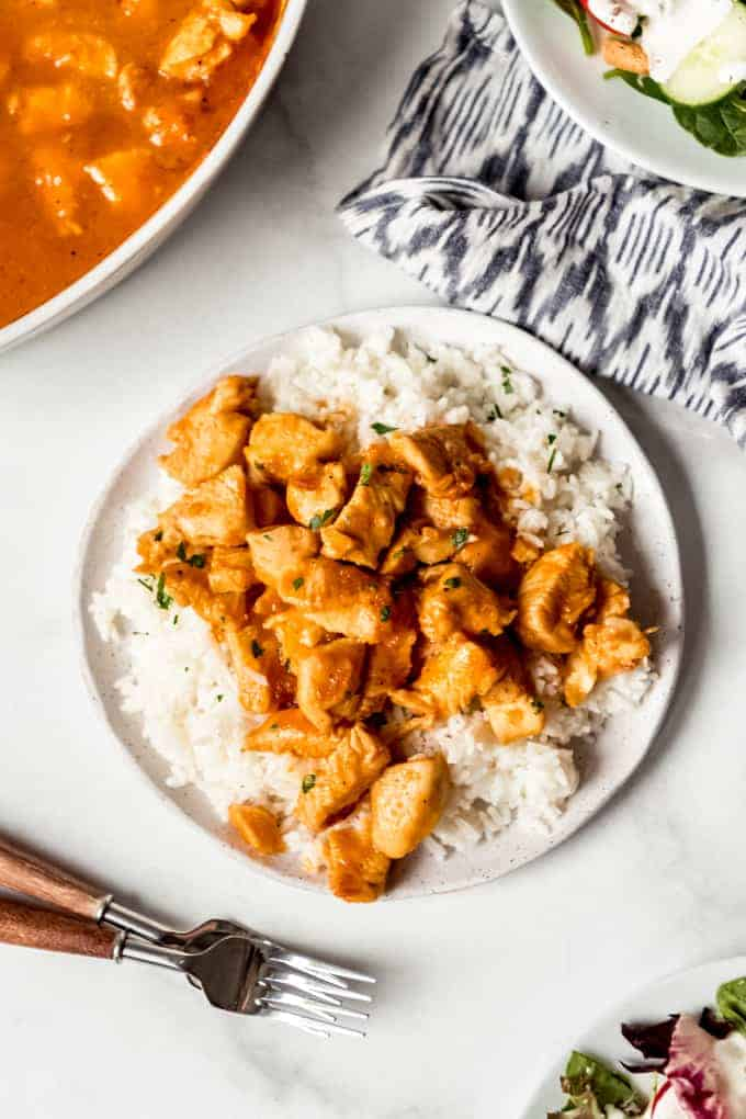 Chunks of Russian chicken over white rice on a plate.