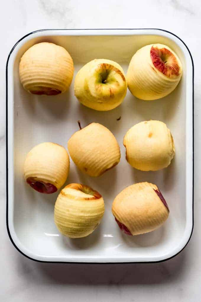 several peeled apples in a baking dish