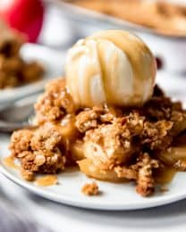 A scoop of caramel drizzled ice cream over a plate full of apple crisp