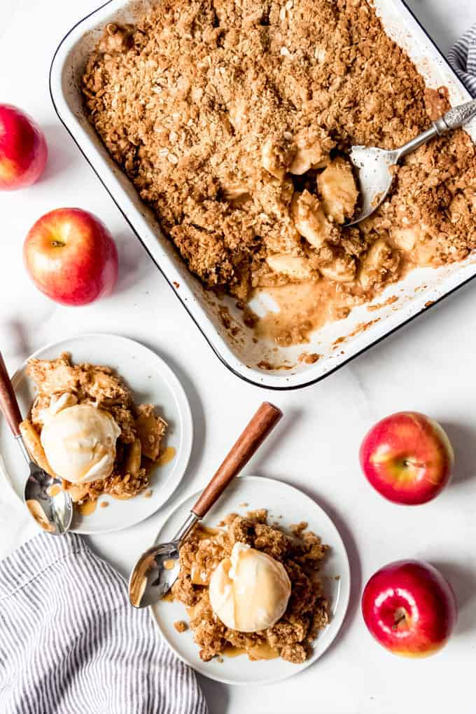 Scoops of apple crisp with vanilla ice cream on plates next to fresh apples and the pan full of the remaining apple crisp.
