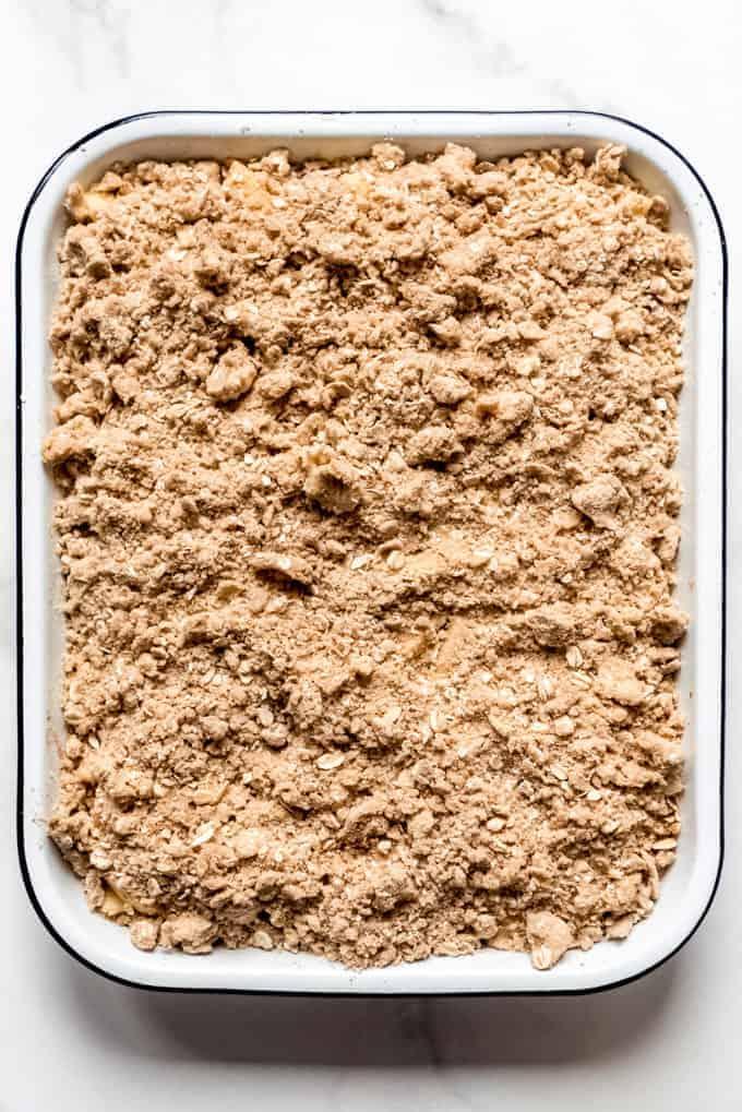 Crisp oat topping sprinkled over a cinnamon apple filling in a white enamel baking dish.