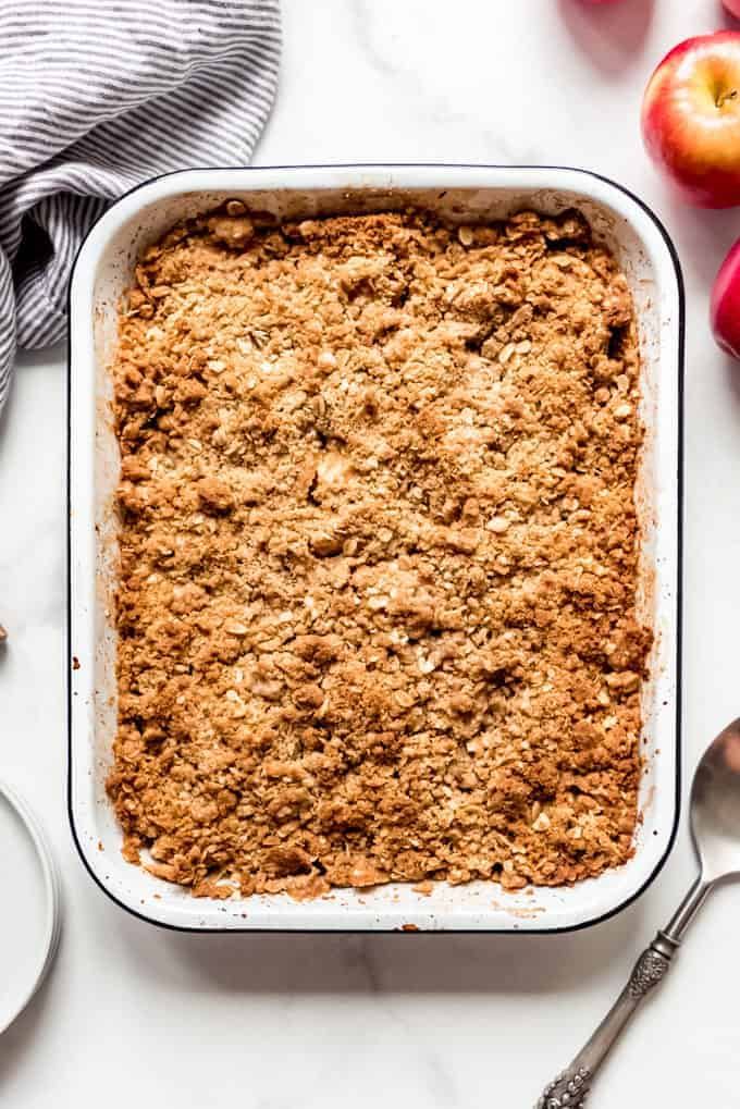 A baked apple crisp next to red apples.