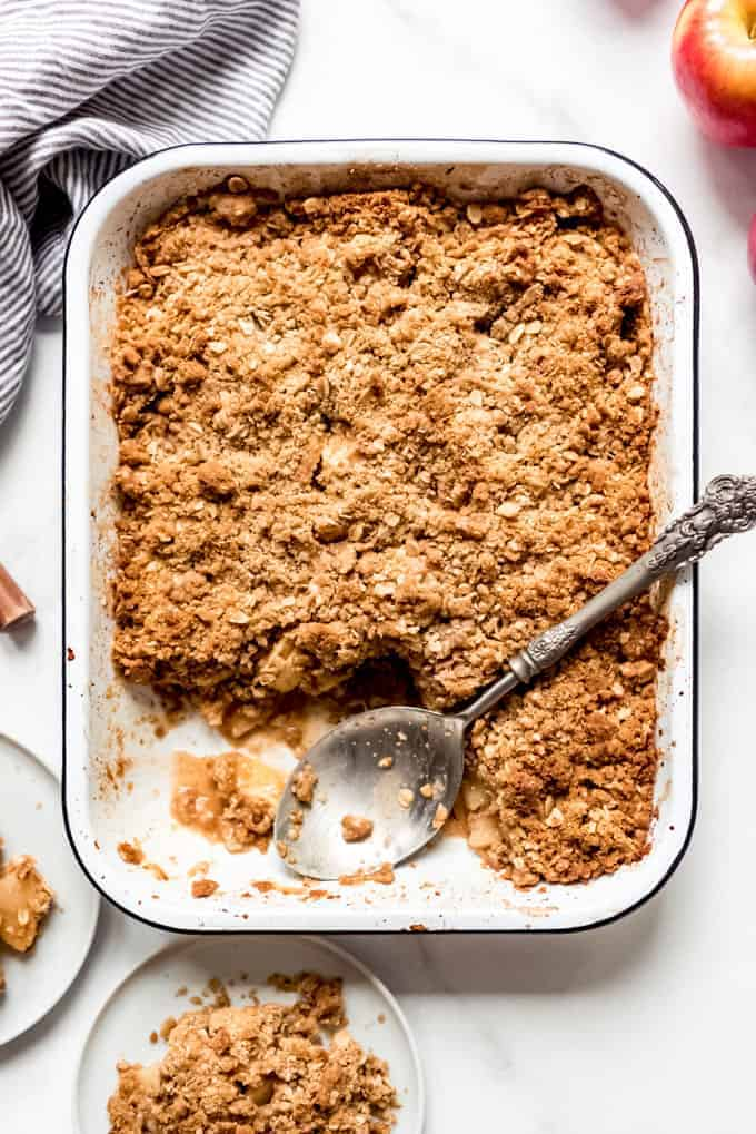 Apple Crisp in a 9x13-inch baking dish with a large serving spoon and a couple servings removed.