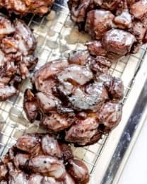 Glazed apple fritters on a wire rack.