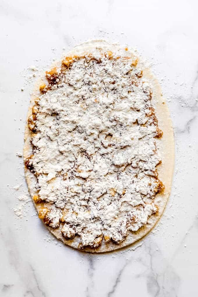 rolled out dough filled with apple mixture and topped with flour
