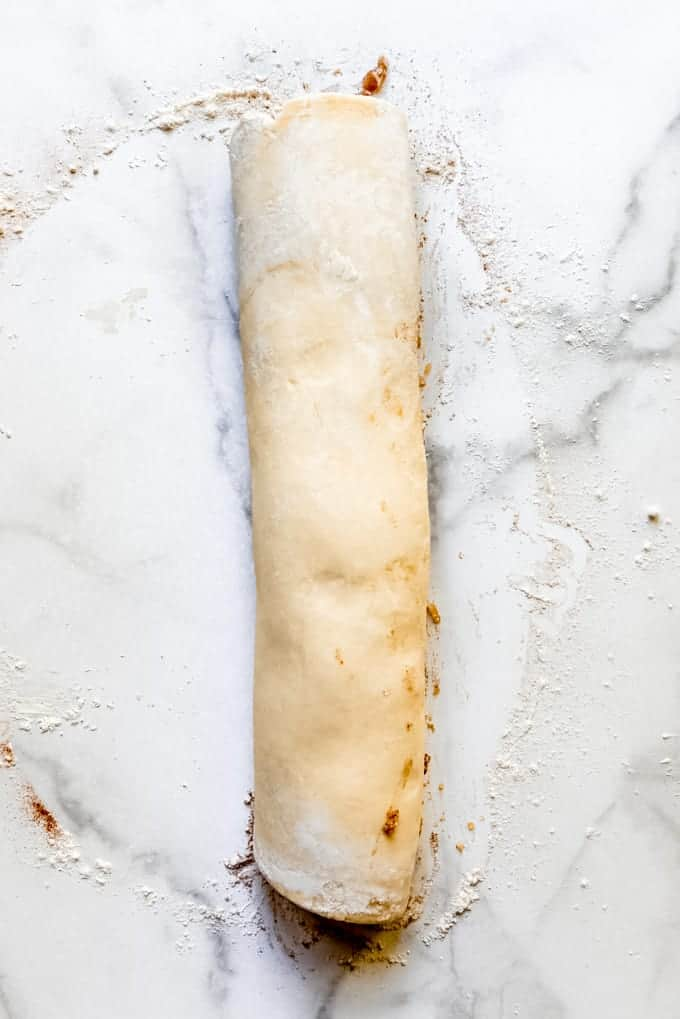 a rolled log of dough and apple filling for making apple fritters