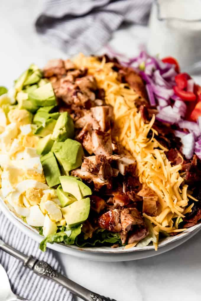 A close image of the top of a bbq chicken cobb salad with hard-boiled eggs, avocado, diced grilled chicken, grated cheddar cheese, bacon, red onion, and tomatoes.