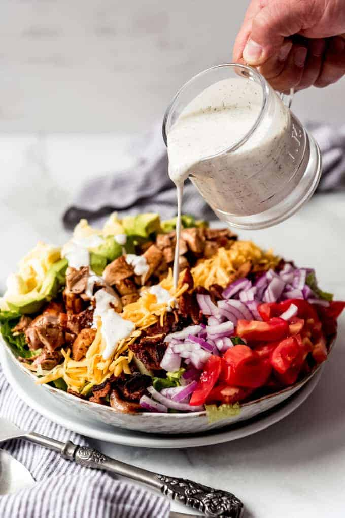 Ranch dressing being poured over a chicken cobb salad.