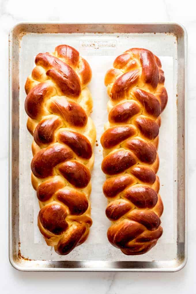 Two loaves of braided challah bread on a baking sheet.