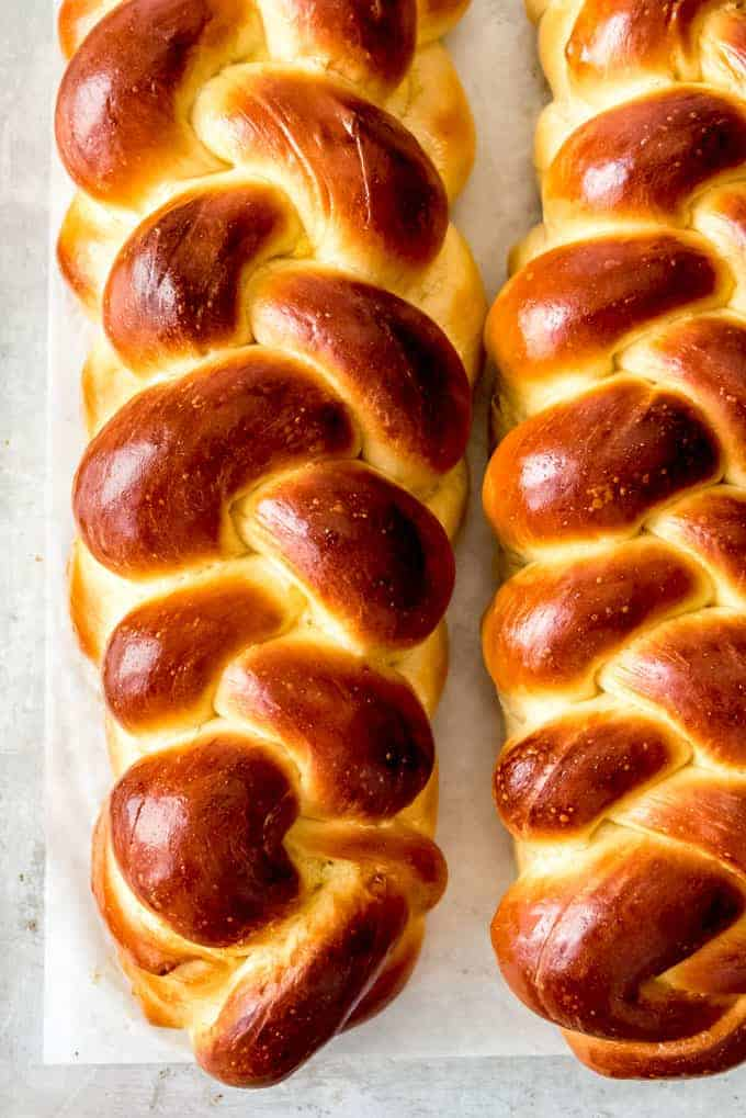 Two loaves of braided challah bread on parchment paper.
