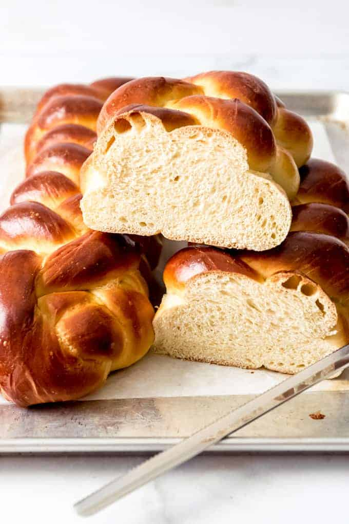 A loaf of challah bread sliced in half sitting on top of another loaf of challah bread.