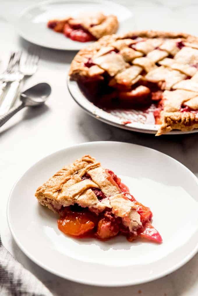 A slice of raspberry peach pie on a white plate in front of the remaining pie in a pie plate.