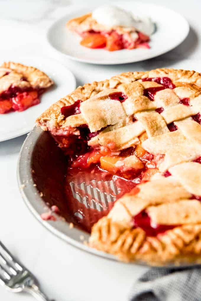 A side view of the juicy filling inside a raspberry peach pie with a flaky lattice crust.