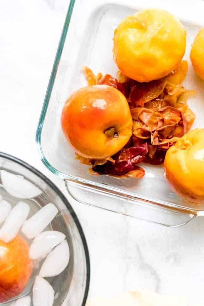 Peeled peaches in a baking dish with a peach in an ice bath to the side