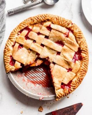 A raspberry peach pie with a lattice crust and a couple slices already cut out.