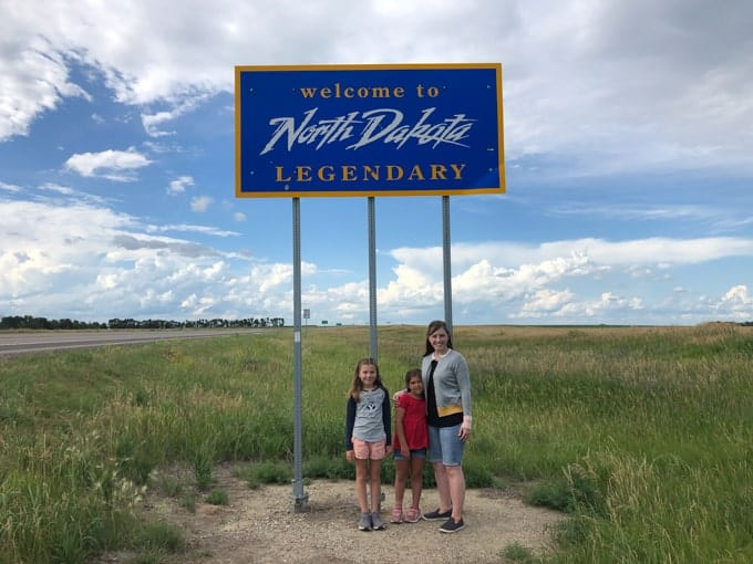 "A mother and daughters in front of the ""Welcome to North Dakota"" sign."