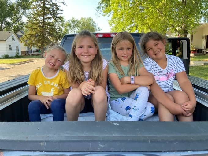 Kids sitting in the back of a truck.
