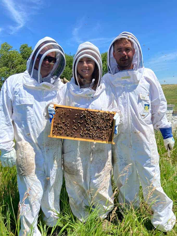 Three people in bee suits holding a frame of honeycomb with bees on it.