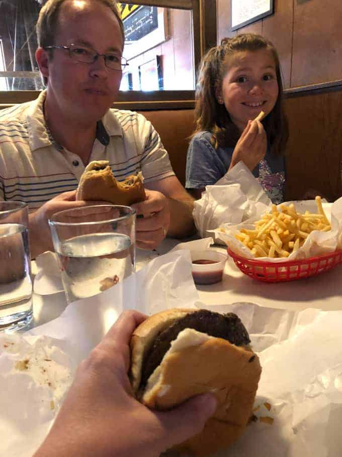 A dad and daughter eating Jucy Lucy burgers and fries.