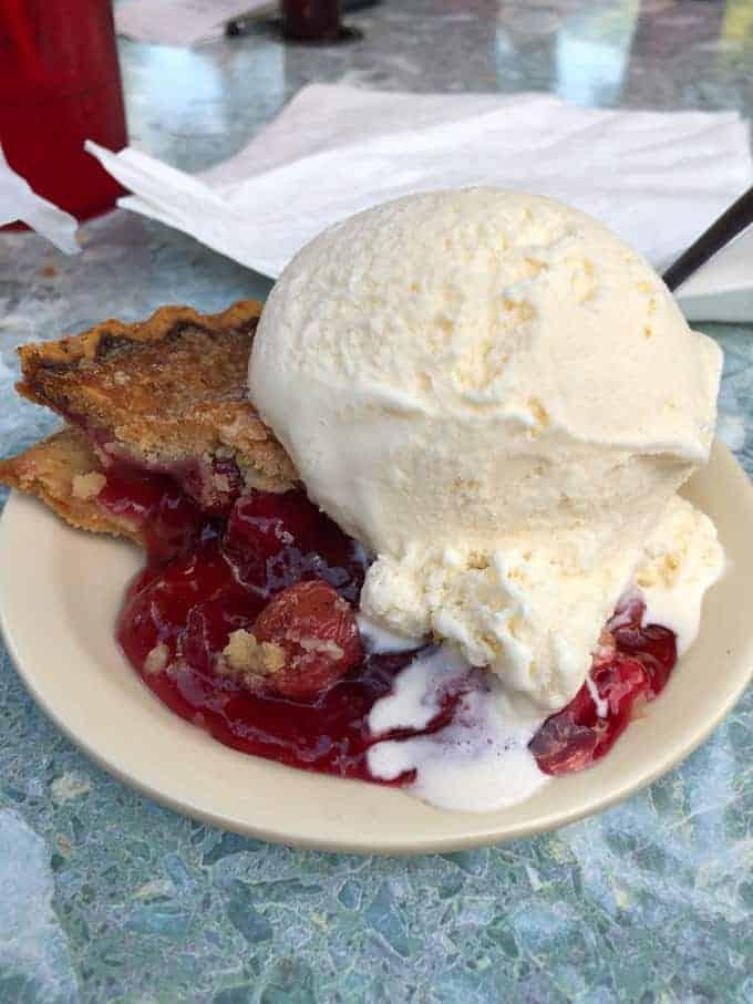 A slice of cherry pie with vanilla ice cream.