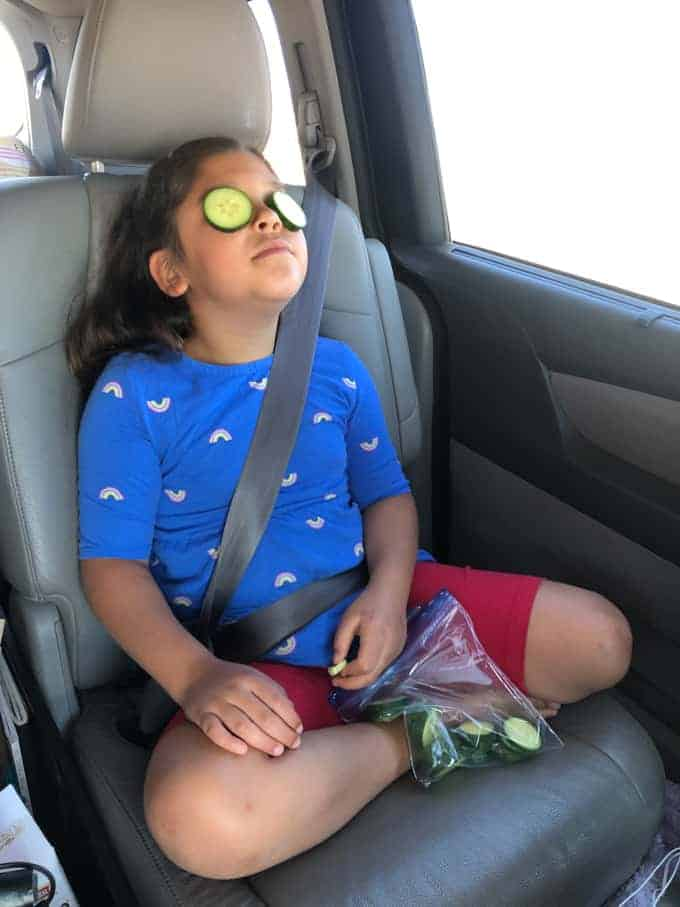 A child sitting in a car on a road trip with cucumber slices on her eyes.