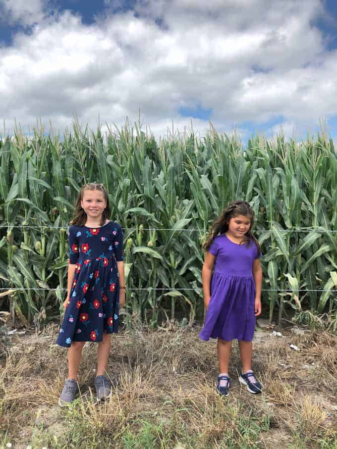 Two girls in front of a corn field.