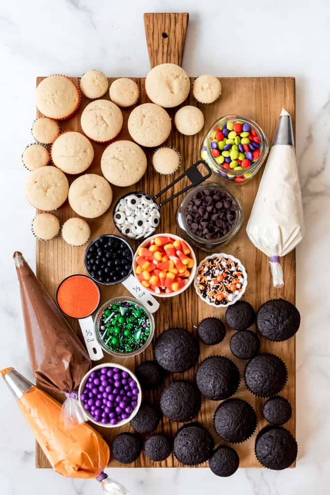 A DIY cupcake board with frosting, sprinkles, candy, and unfrosted cupcakes.