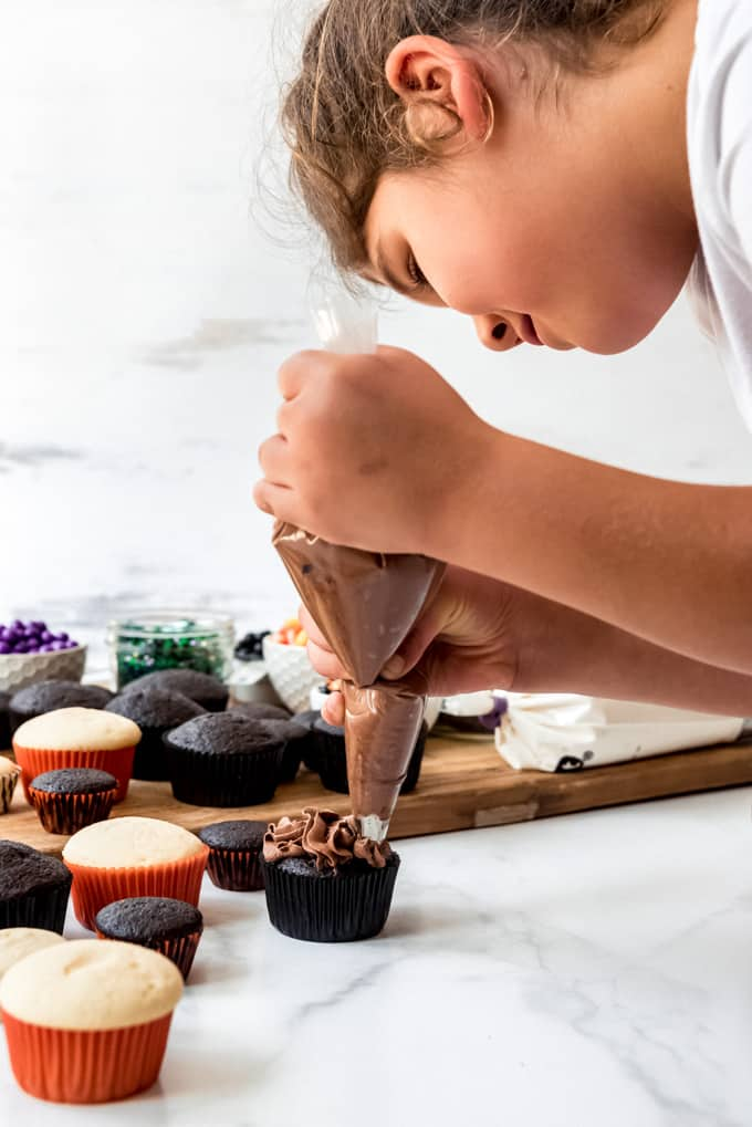 A child piping chocolate frosting onto a cupcake.