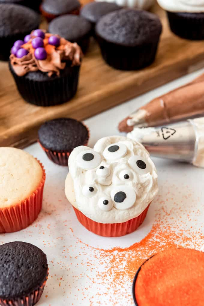 A white cupcake with vanilla frosting and googly eye candies on top.