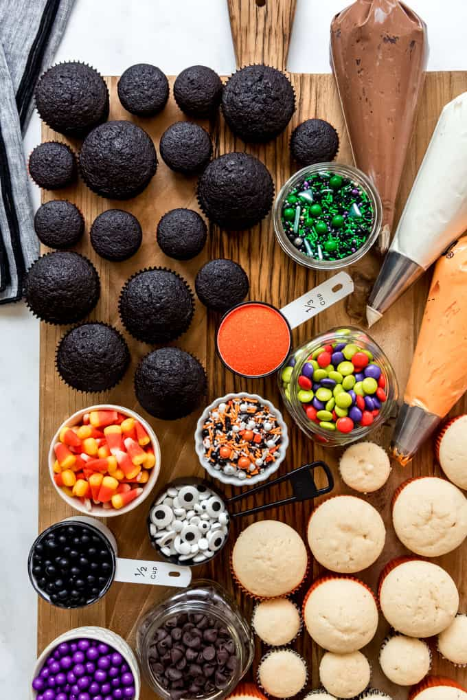 A decorate-your-own cupcake board with Halloween sprinkles and frosting.